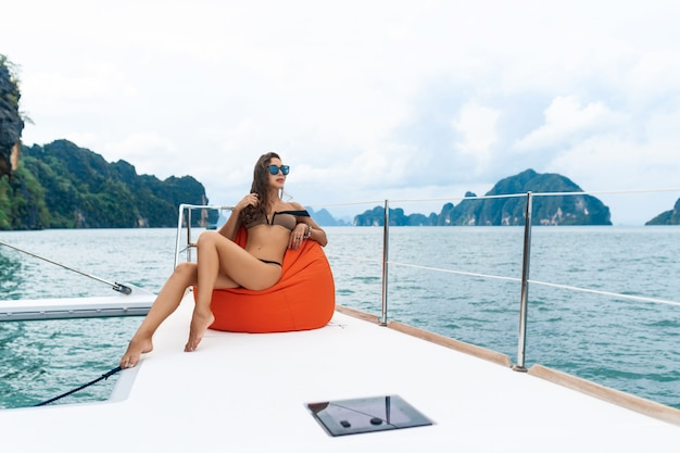 Modeporträt eines positiven und schönen mädchens, das auf dem orangefarbenen kissen sitzt. attraktive brünette, die mit dem fernglas in den händen lächelt und posiert. model trägt ein modekleid beim segeln