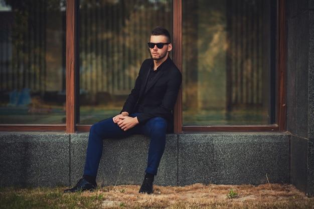 Modeporträt im freien des jungen stilvollen mannes