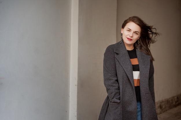 Modeporträt im freien des schönen modernen mädchens, das in der straße, kopie, leerer raum aufwirft