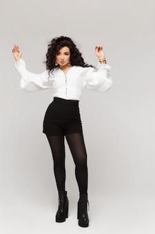Modeporträt in voller länge einer jungen frau in einer trendigen weißen bluse und schwarzen shorts, die über ...