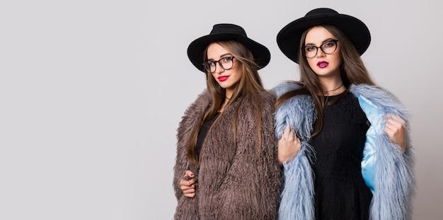 Modeporträt von zwei eleganten frauen, beste freunde, die innen auf grauer wand posieren, die flauschigen wintermantel, schwarzen freizeithut tragen. moderne kleidung. schwestern gehen.