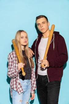 Modeporträt von zwei jungen coolen hipster-mädchen und jungen, die jeans mit baseballschlägern tragen