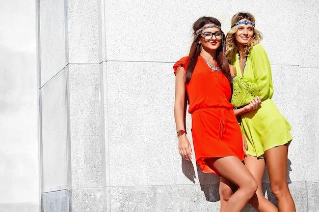 Modeporträt von zwei jungen hippie-frauenmodellen im sonnigen sommertag in hellen bunten hipster-kleidern