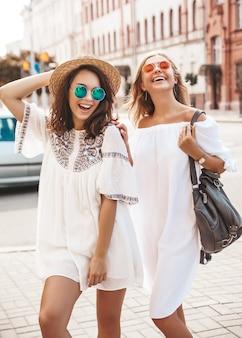 Modeporträt von zwei jungen stilvollen hippie-brünetten und blonden frauen im sonnigen sommertag. models in weißen hipster-klamotten. frauen posieren. werde verrückt