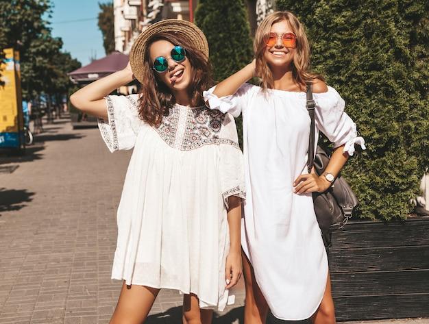 Modeporträt von zwei jungen stilvollen hippie-brünetten und blonden frauen im sonnigen sommertag. models in weißen hipster-klamotten. frauen posieren