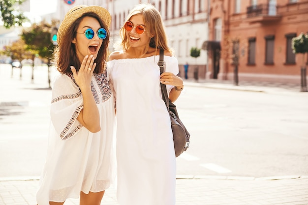 Modeporträt von zwei jungen stilvollen hippie-brünetten- und blonden frauenmodellen. beste freunde im weißen sommer hipster kleid posieren