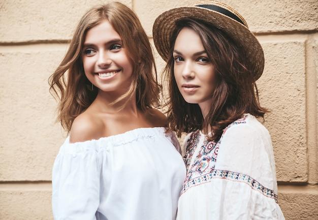 Modeporträt von zwei jungen stilvollen hippie-brünetten- und blonden frauenmodellen im sonnigen sommertag in den weißen hipster-kleidern, die nahe gelber wand aufwerfen. kein make up