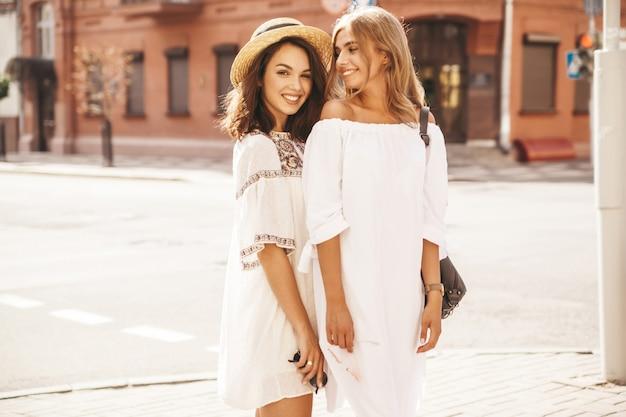 Modeporträt von zwei jungen stilvollen hippie-brünetten- und blonden frauenmodellen im sonnigen sommertag in der weißen hipster-kleidung, die aufwirft. kein make up