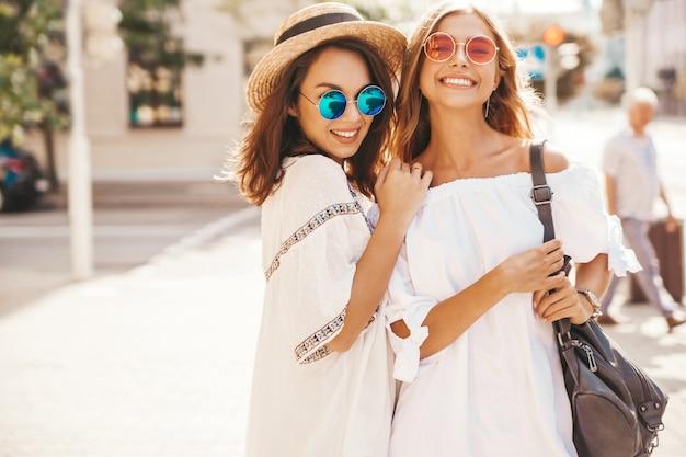 Modeporträt von zwei jungen stilvollen hippie-brünetten- und blonden frauenmodellen im sonnigen sommertag in der weißen hipster-kleidung, die aufwirft