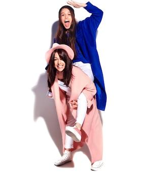 Modeporträt von zwei lächelnden brünetten frauenmodellen im sommer lässigen hipster-mantel lokalisiert auf weiß. mädchen halten sich gegenseitig auf dem rücken