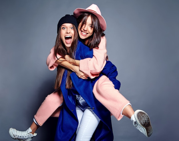 Modeporträt von zwei lächelnden brünetten frauenmodellen im sommer lässigen hipster-mantel posiert. mädchen halten sich gegenseitig auf dem rücken