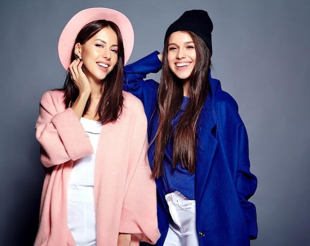 Modeporträt von zwei lächelnden brünetten frauenmodellen im sommer lässigen hipster-mantel posiert