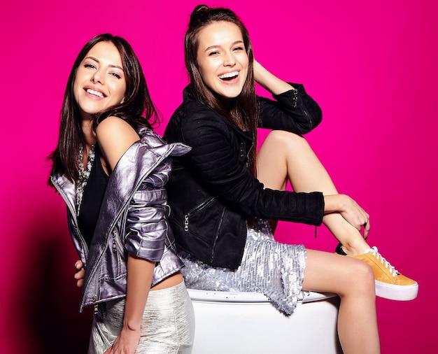Modeporträt von zwei lächelnden brünetten modellen im sommer schwarze lässige hipster-kleidung, die auf rosa posiert, auf weißem fass sitzend