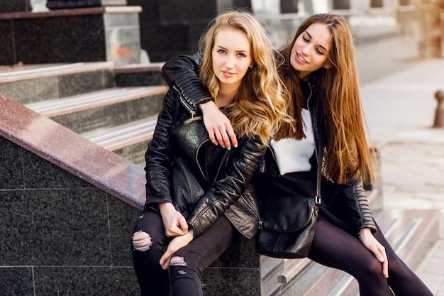 Modeporträt von zwei stilvollen hübschen frauen, die auf der straße in sonnigem tag aufwerfen. trägt ein trendiges urbanes outfit, eine lederjacke und stiefelabsätze. junge freunde warten auf treppen im freien.