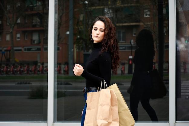 Modeporträtfrau mit einkaufstaschen, die schwarzes outfit mit hut auf gelber wand tragen tragen.