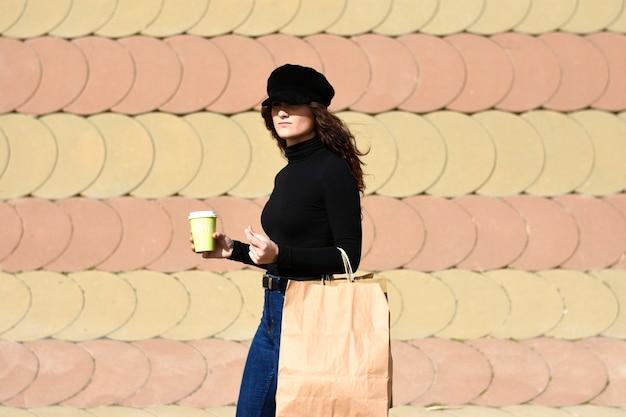 Modeporträtfrau mit einkaufstaschen, die schwarzes outfit mit hut tragen, während sie einen kaffee zum mitnehmen halten
