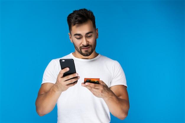 Modern unter verwendung der kreditkarte mit telefon durch intelligenten jungen mann