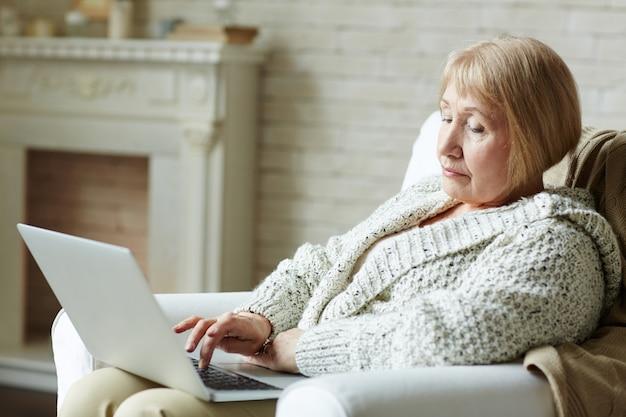 Moderne ältere frau, die das netz surft