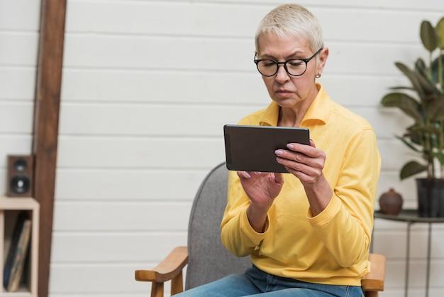 Moderne ältere frau, die eine tablette hält