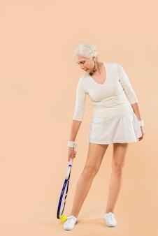 Moderne ältere frau, die tennis spielt