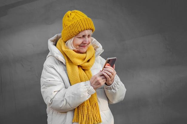 Moderne ältere frau in oberbekleidung mit smartphone.
