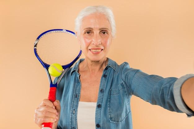 Moderne ältere frau mit dem tennisschläger, der selfie nimmt