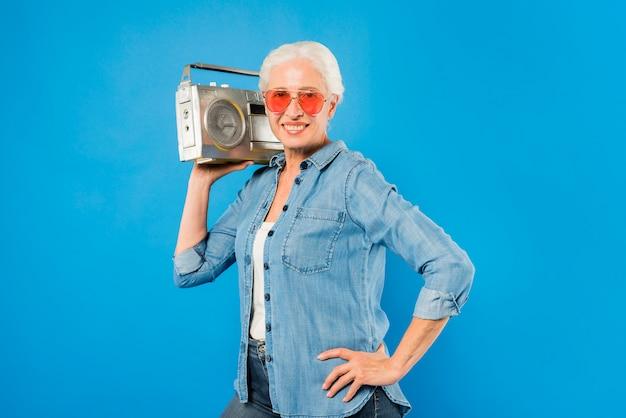 Moderne ältere frau mit weinleseradio