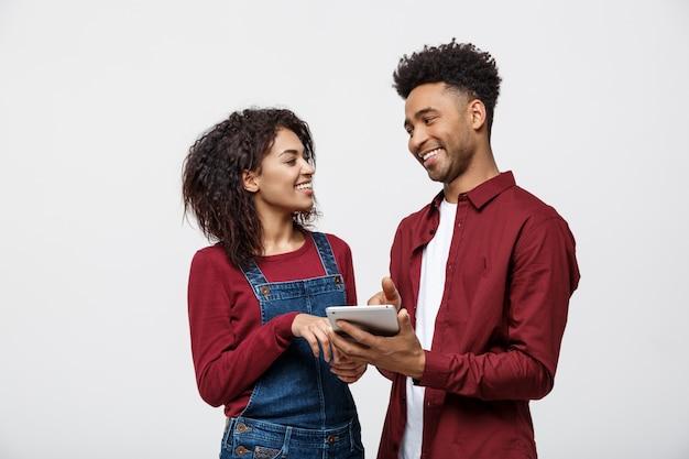 Moderne afroamerikanerleute, die an tablette mit lokalisiert auf weißem hintergrund arbeiten.