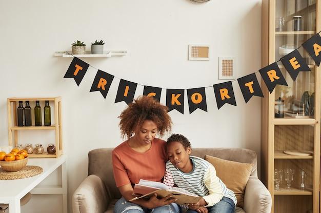 Moderne afroamerikanische mutter, die auf sofa im wohnzimmer mit ihrem kleinen sohn sitzt, der gruselige halloween-geschichten liest