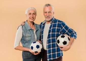 Moderne ältere Paare mit Fußball