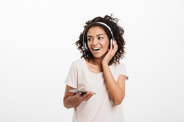 Moderne amerikanische frau mit afro-frisur und großem lächeln, das musik über drahtlose kopfhörer hört und handy in der hand hält, lokalisiert über weißer wand