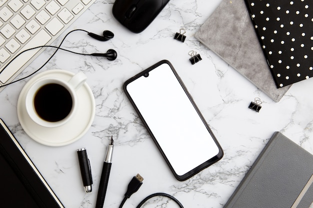 Moderne arbeitsplatzanordnung auf marmor mit leerem telefon