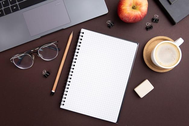 Moderne arbeitsplatzanordnung mit leerem notizbuch