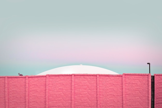 Moderne architektur, ufo hinter einer rosa backsteinmauer