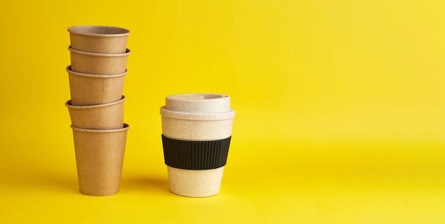 Moderne art von zero waste. ein wiederverwendbarer bambusbecher gegen viele einweg-pappbecher. kaffee und ökologie. gelbes banner mit textfreiraum