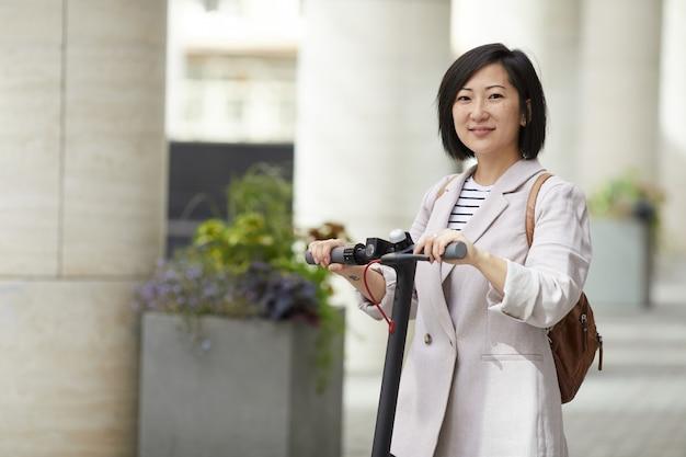 Moderne asiatische frau, die mit roller aufwirft
