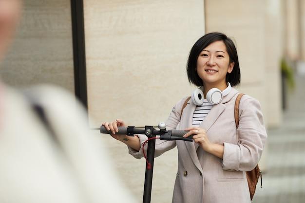 Moderne asiatische frau, die roller reitet