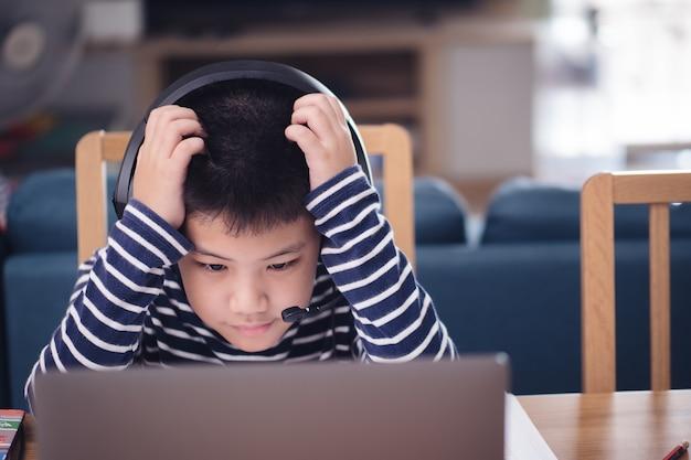 Moderne asiatische kinder lernen online, schauen auf den laptop-bildschirm, kratzen sich am kopf, fühlen sich beim lernproblem schwindlig. technologiebildungskonzept arbeit von zu hause aus