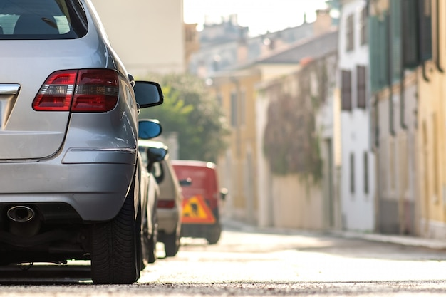 Moderne autos, die auf der straßenseite der stadt im wohngebiet geparkt werden. glänzende fahrzeuge am bordstein geparkt. konzept der städtischen verkehrsinfrastruktur.