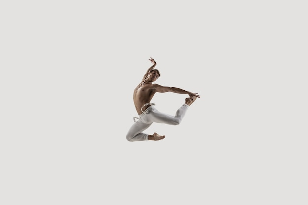 Moderne balletttänzerin. ballett für zeitgenössische kunst. junge flexible athletische mann. studioaufnahme isoliert auf weißem hintergrund. negativer raum.