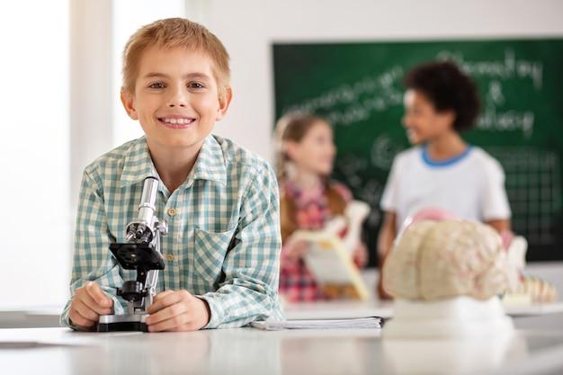 Moderne bildung. fröhlicher glücklicher schuljunge, der vor dem mikroskop steht, während er zu ihnen lächelt