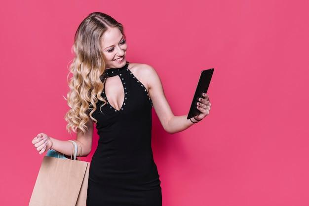 Moderne blondine mit der papiertüte, die selfie nimmt