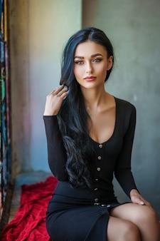 Moderne brunettefrau im schwarzen kleid, das nahe dem buntglasfenster sitzt