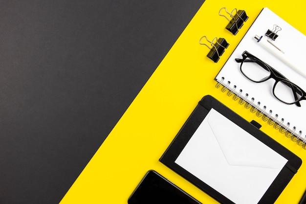 Moderne büro-schreibtisch-wohnung lag mit notizblock aus spiralpapier, modell mit weißen umschlägen und lesebrille auf schwarz-gelber oberfläche
