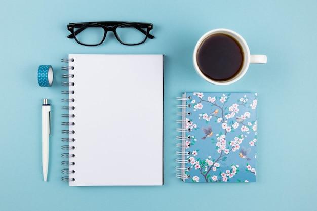 Moderne büroarbeitsplatzwohnung lag mit leerem papierspiral-notizbuchmodell, stift, lesebrille und schwarzem kaffee oder tee auf blauer oberfläche