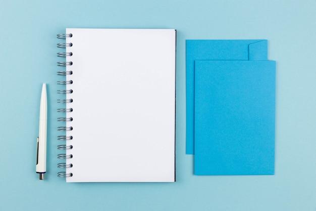 Moderne büroarbeitsplatzwohnung lag mit leerem spiralpapier-notizbuchmodell, leerem umschlag und stift auf blauer oberfläche