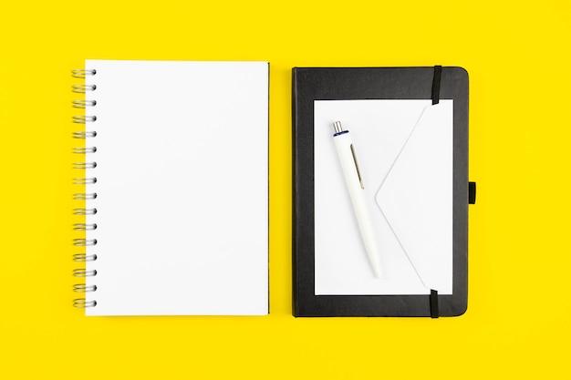Moderne büroarbeitsplatzwohnung lag mit leerem spiralpapier-notizbuchmodell, leerem umschlag und stift auf gelber oberfläche
