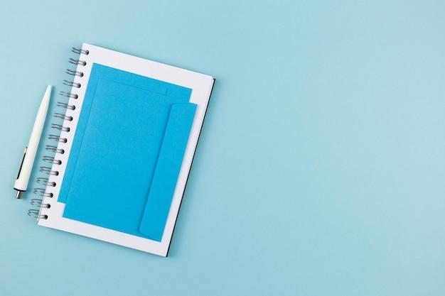 Moderne büroarbeitsplatzwohnung lag mit spiralpapier-notizbuch, leerem umschlagmodell und stift auf blauer oberfläche