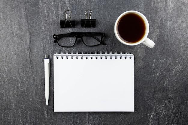Moderne büroarbeitsplatzwohnung lag mit spiralpapier-notizbuchmodell, lesebrille, stift und schwarzem kaffee oder tee auf dunkler oberfläche