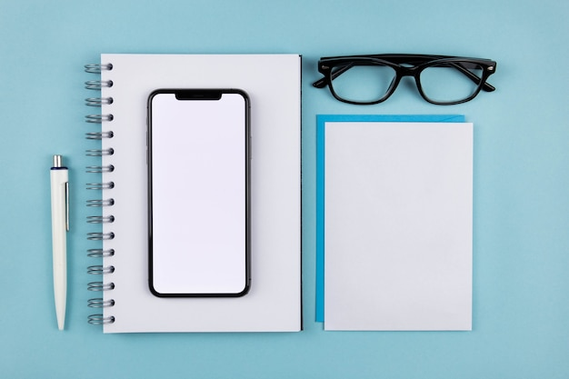 Moderne büroschreibtischwohnung mit smartphone-bildschirmmodell, notizblock aus spiralpapier, leeren weißen umschlägen und lesebrille auf blauer oberfläche